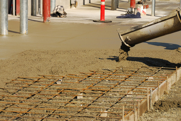 Workers pouring a concrete pad outside a new commercial building.