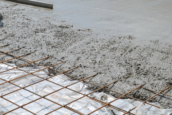 Wet concrete cement flowing over rebar metal